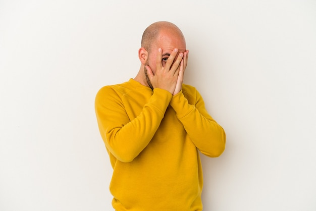 Young bald man isolated on white background blink through fingers frightened and nervous.