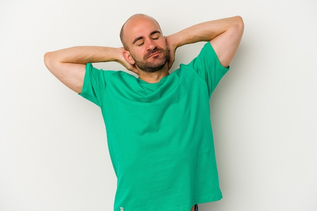 Young bald man isolated on white background feeling confident, with hands behind the head.