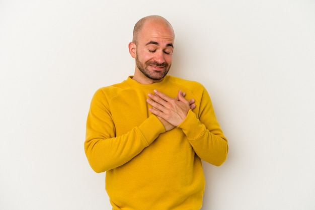 Young bald man isolated on white background has friendly expression, pressing palm to chest. love concept.