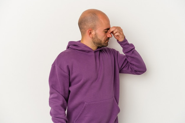 Young bald man isolated on white background having a head ache, touching front of the face.
