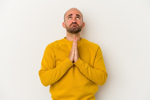Young bald man isolated on white background holding hands in pray near mouth, feels confident.