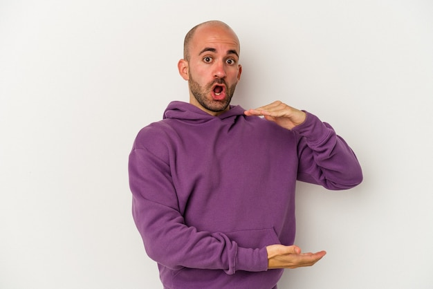 Young bald man isolated on white background holding something with both hands, product presentation.