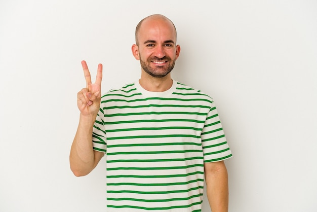 Young bald man isolated on white background joyful and carefree showing a peace symbol with fingers.
