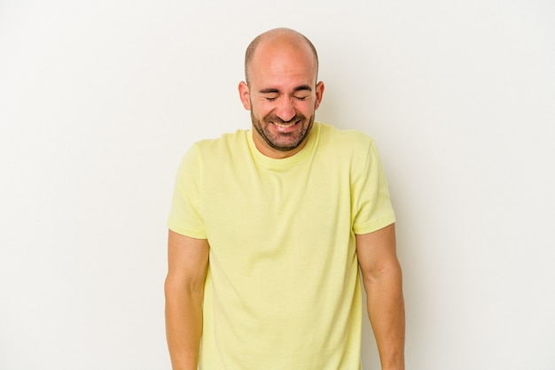 Young bald man isolated on white background laughs and closes eyes, feels relaxed and happy.