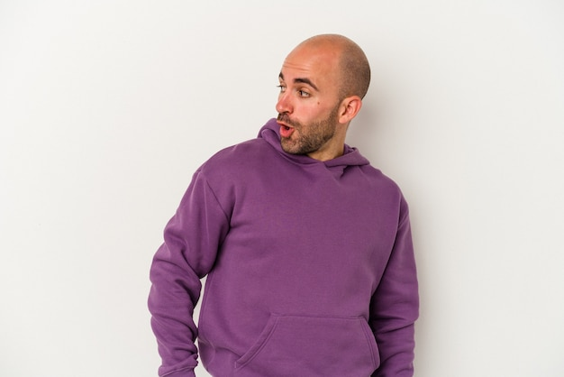 Young bald man isolated on white background looks aside smiling, cheerful and pleasant.
