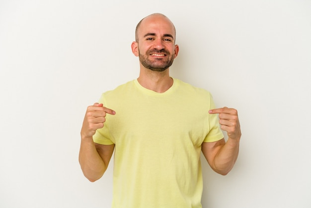 Young bald man isolated on white background points down with fingers, positive feeling.