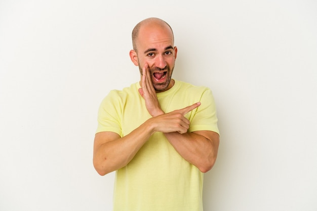 Young bald man isolated on white background saying a gossip, pointing to side reporting something.