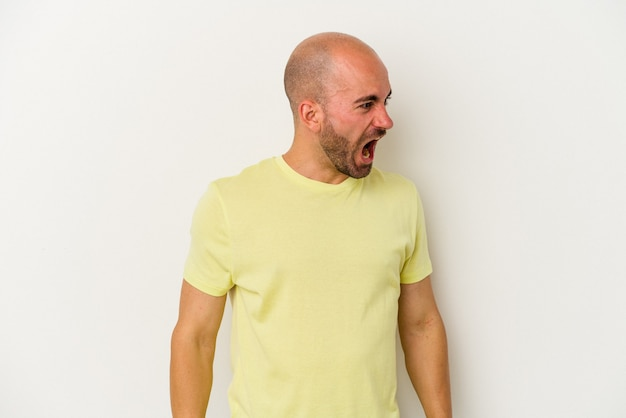 Young bald man isolated on white background shouting very angry, rage concept, frustrated.