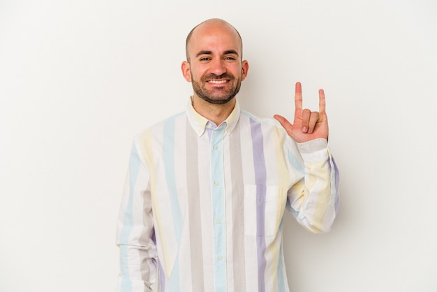 Young bald man isolated on white background showing a horns gesture as a revolution concept.