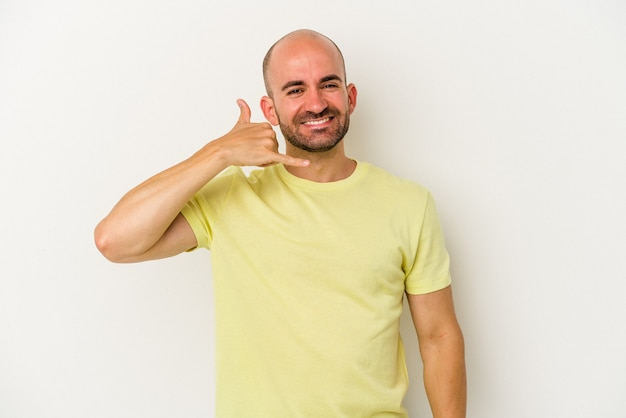Young bald man isolated on white background showing a mobile phone call gesture with fingers.