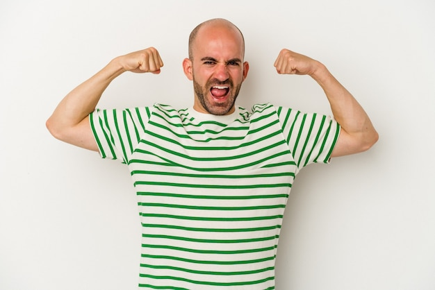 Young bald man isolated on white background showing strength gesture with arms, symbol of feminine power