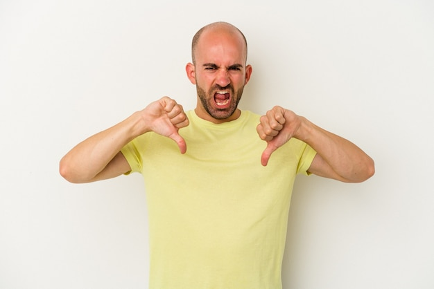 Young bald man isolated on white background showing thumb down and expressing dislike.