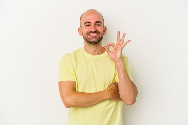 Young bald man isolated on white background winks an eye and holds an okay gesture with hand.