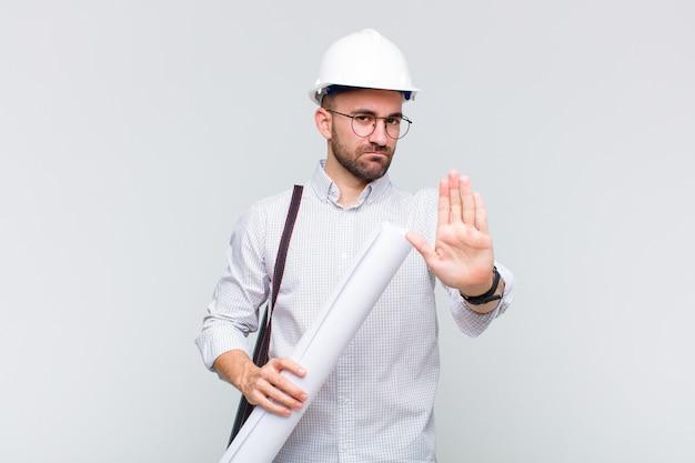 Молодой лысый мужчина выглядит серьезным, строгим, недовольным и злым, показывая открытую ладонь, делая стоп-жест
