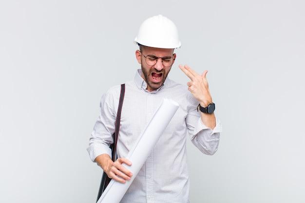 Молодой лысый мужчина выглядит несчастным и подчеркнутым, жест самоубийства делает знак пистолета рукой, указывая на голову
