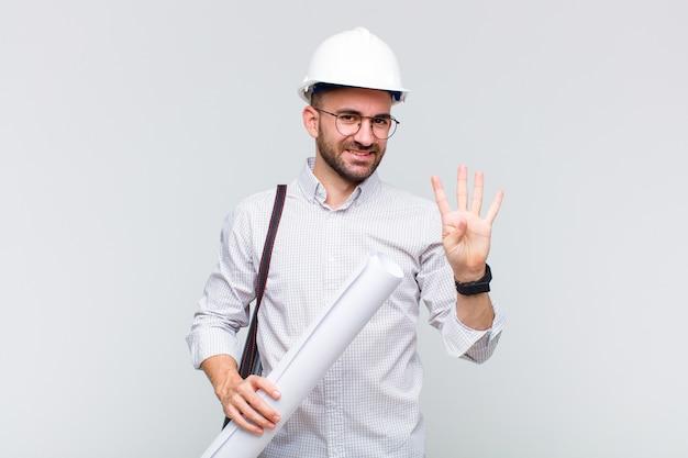 Молодой лысый мужчина улыбается и выглядит дружелюбно, показывает номер четыре или четвертый с рукой вперед, отсчитывая