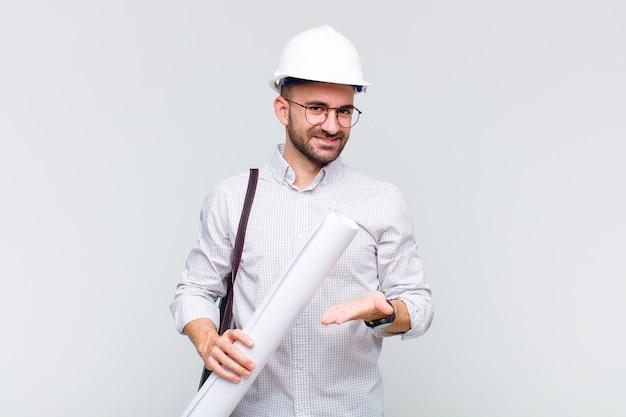 유쾌하게 웃고, 행복감을 느끼고 손바닥으로 복사 공간에 개념을 보여주는 젊은 대머리 남자
