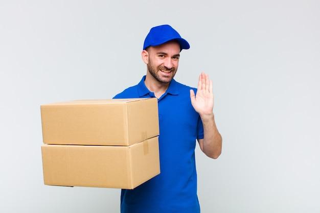 Молодой лысый мужчина счастливо и весело улыбается, машет рукой, приветствует и приветствует вас или прощается