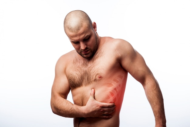 Young bald man sportive physique holds on sore rib
