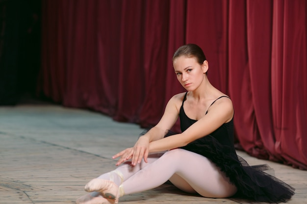 Young ballerina in black dress trains behind the scenes.