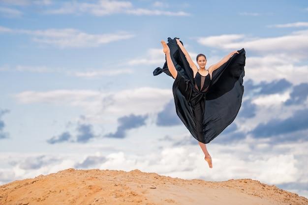 Young ballerina in a black long dress dancing