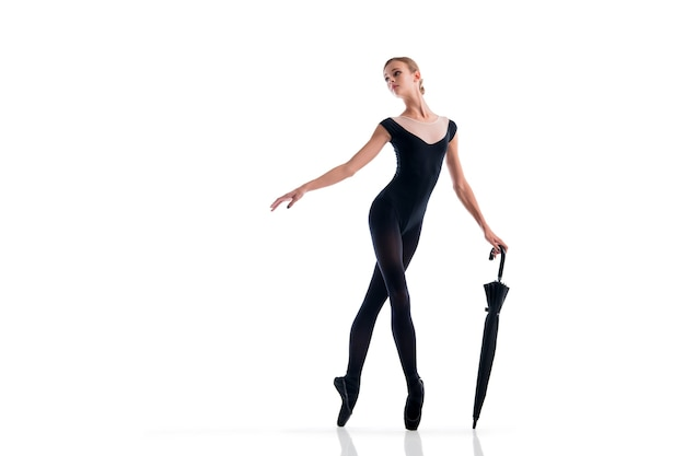 A young ballerina in black pointe shoes and leotard posing with umbrella in graceful pose isolated on white background