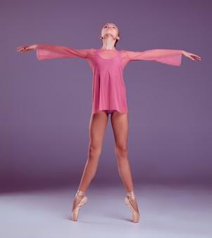 Молодая балерина в розовом платье показывает свои техники на сиреневом фоне