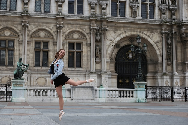 A young ballerina dances in the street of paris