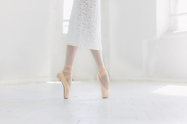 Young ballerina dancing, closeup on legs and shoes, standing in pointes