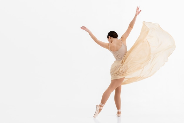 Young ballerina dancing with copy space