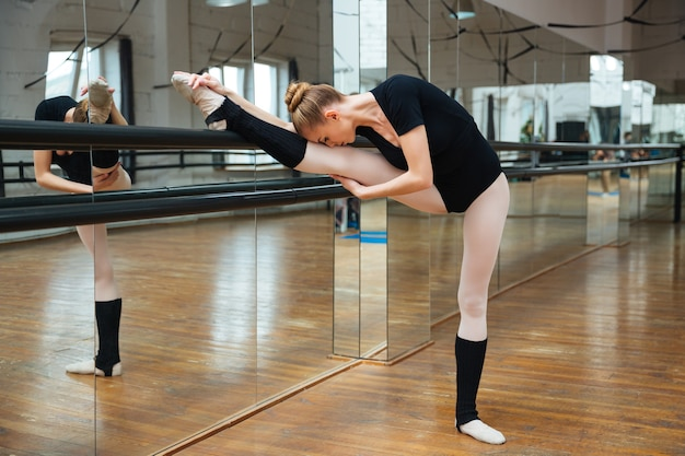 Young ballerina doing stretching exercises in ballet class