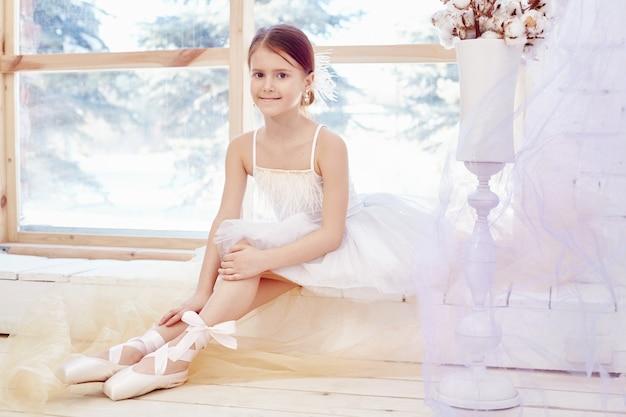 어린 발레리나 소녀가 발레 공연을 준비하고 있습니다. 리틀 프리마 발레. 하얀 볼 가운을 입은 소녀와 창가 근처의 포인트, 아름다운 빨간 머리. 젊은 연극배우