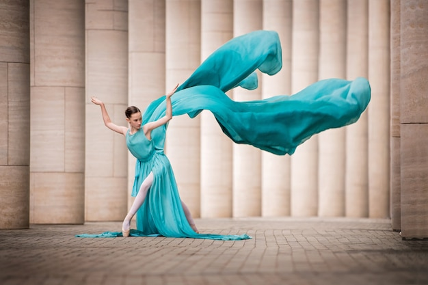 Young ballerina girl stands in a graceful pose in a dress, develops like wings among tall columns