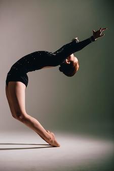 Young ballerina having exercises in the studio