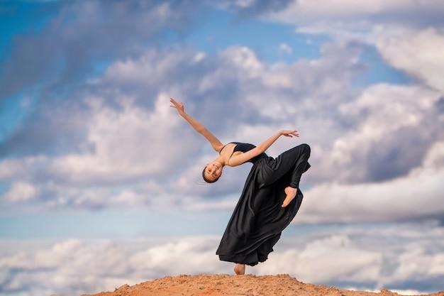 Молодая балерина в черном длинном платье танцует