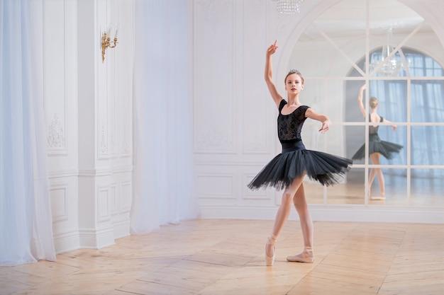 검은 투투를 입은 젊은 발레리나가 거울 앞의 커다란 밝은 홀에서 포인트 위에서 춤을 추고 있습니다.