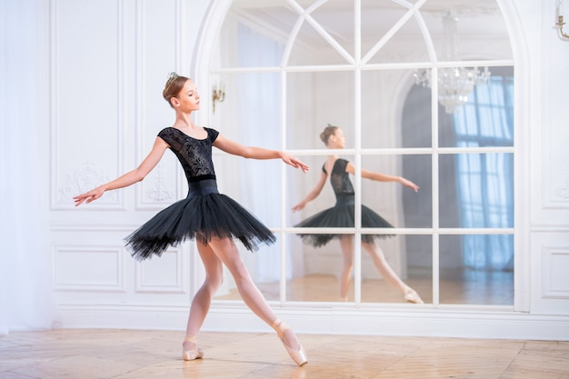 Юная балерина в черной пачке стоит в изящной позе на пуантах в большом светлом зале перед зеркалом.