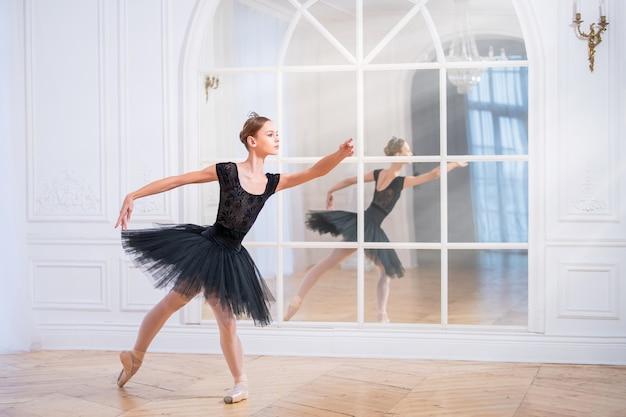 검은 투투를 입은 젊은 발레리나는 거울 앞의 커다란 밝은 홀에서 포인트 슈즈를 신고 우아한 포즈를 취하고 있습니다.