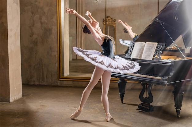 빈티지 인테리어의 아름다운 오래된 피아노에 흰색 투투 춤의 젊은 발레리나