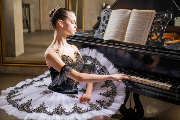 흰색 발레 용 스커트를 입은 젊은 발레리나가 아름다운 오래된 피아노를 연주합니다.