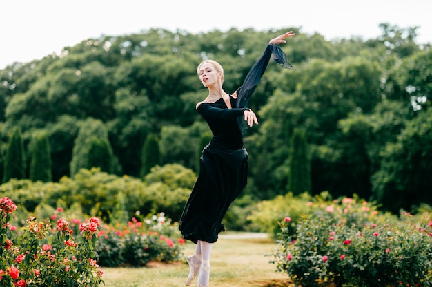 公園のバラの茂みの中でジャンプ黒のドレスの若いバレリーナ。