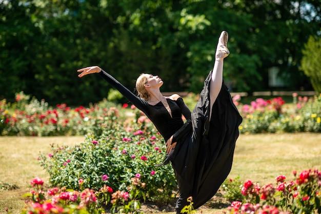 夏の公園でポーズとバレエのポーズを示す黒のドレスの若いバレリーナ。