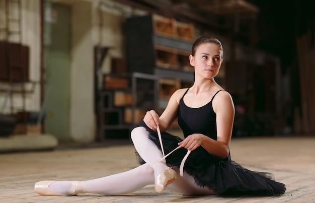 Юная балерина в черном платье тренируется за кадром.
