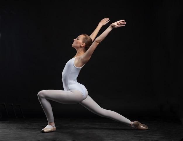 黒の背景に分離された体操ポーズの白い体の若いバレリーナ