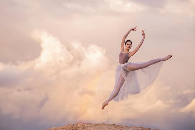 Young ballerina in a long dress dancing