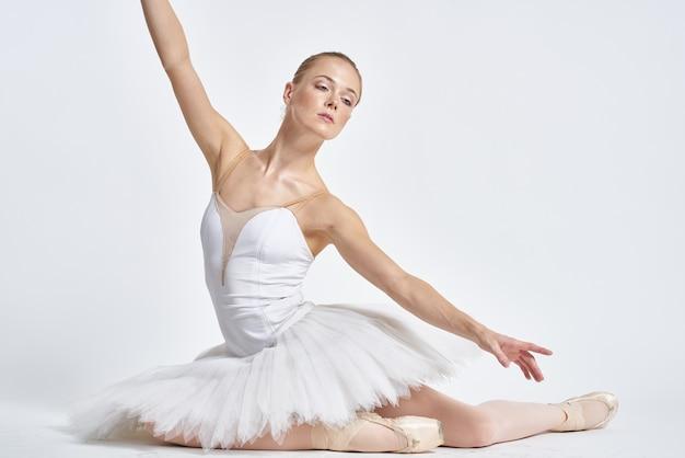 Молодая балерина позирует. белый фон.