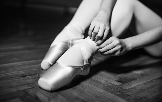 座っている若いバレリーナ、足と金色の靴。