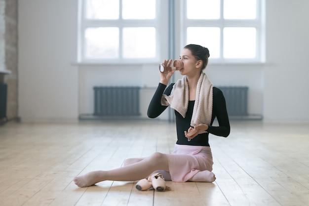 床に座って、ダンススタジオでダンスの後に水を飲む若いバレリーナ