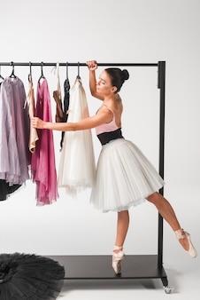 Young ballerina standing on tiptoe choosing tutu from hangers