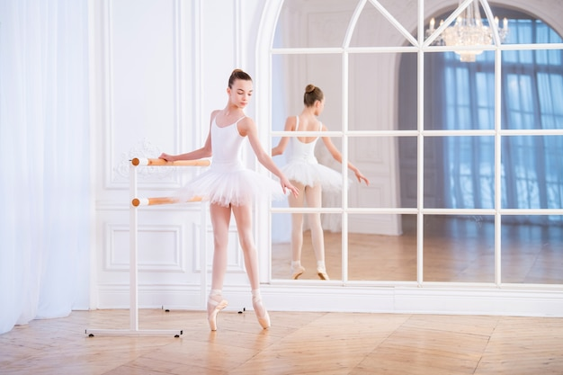 Young ballerina stands on pointe shoes at a ballet barre in a beautiful white hall in front of a mirror.